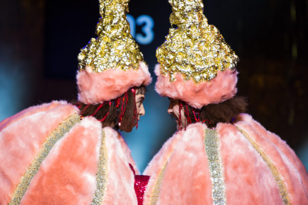 Tow performers dressing like pink pumpkins starring at each other, while their foreheads are touching each other's