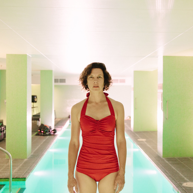a woman in red bathing suit in front of a pool