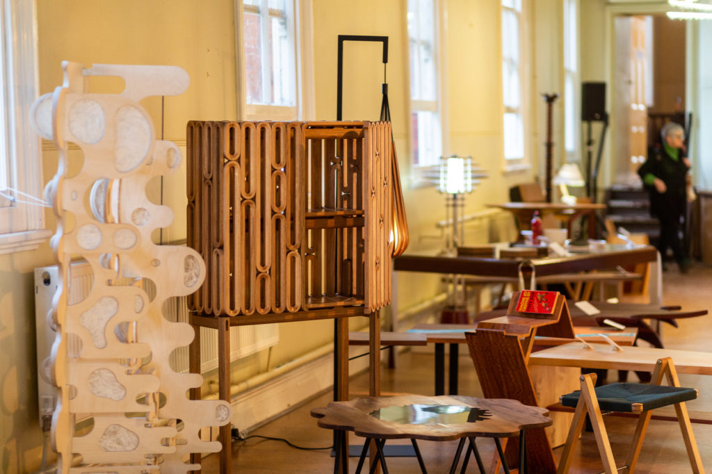 A picture of a previous Fringe Furniture exhibition, showcasing pieces including a tall white shelf with lots of curves, and short brown coffee table shaped like a flower and a retro brown wooden cabinet with long, cylindrical shapes.