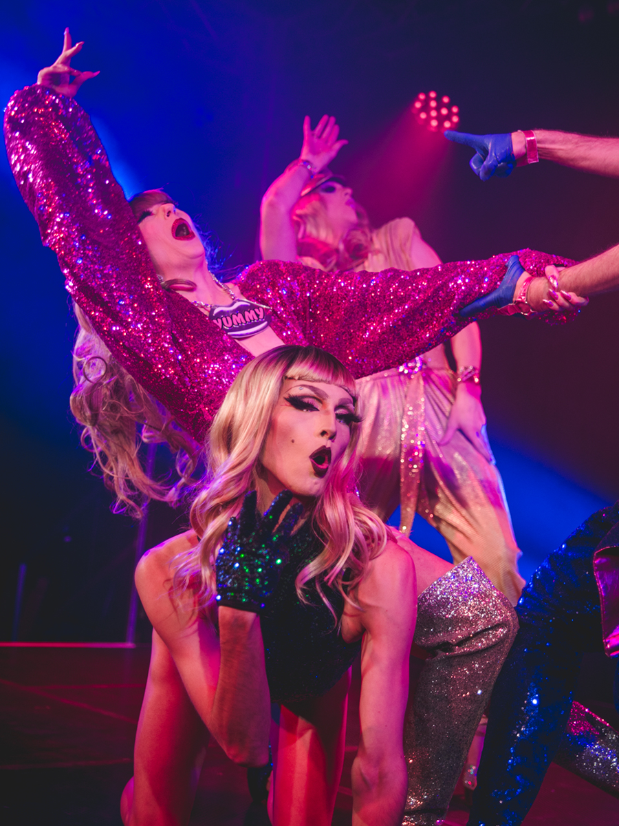 Three performers are wearing sequinned colourful costumes on stage. In the foreground is a performer on hands and knees singing and looking at the camera, wearing drag-style makeup, long blonde hair, with a green sequinned gloved hand held up to their face. The two performers behind are leaning back with one arm in the air, also singing and holding onto an arm that appears from out of shot. One wears a necklace that says 'YUMMY'. In the background is blue and pink stage lighting.