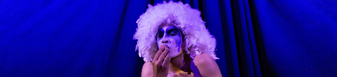 A banner image of a performer with a white feathery wig and a white and blue painted face, putting an egg up to their mouth. The background is a blue curtain.