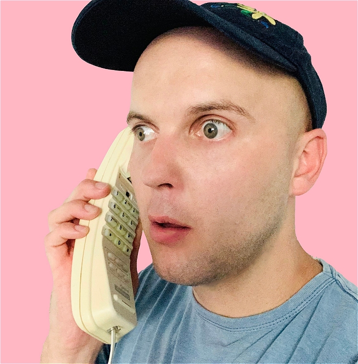 A guy in a navy blue cape with a blue t shirt on a hotel landline phone. The phone is from the 1990s. The guy is looking slightly shocked.