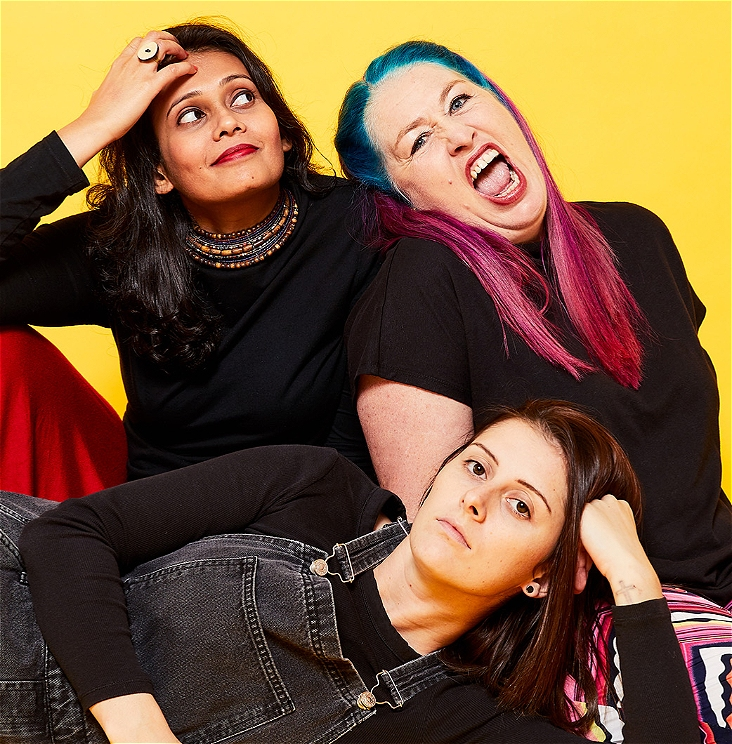 The image is a portrait of the Take 3 trio sitting against a bright yellow background. Kru Harale is South Asian, has long black hair and wears a black skivvy over a red skirt. She looks off camera with a small smile. Kelly Mac is Caucasian, has long pink and blue hair and wears a black t-shirt over multi-coloured pants. She looks directly at the camera with an open-mouthed snarl. Annie Boyle is Caucasian and lies in front of the other two women. She has shoulder-length brown hair. She wears grey overalls and looks blankly at the camera.