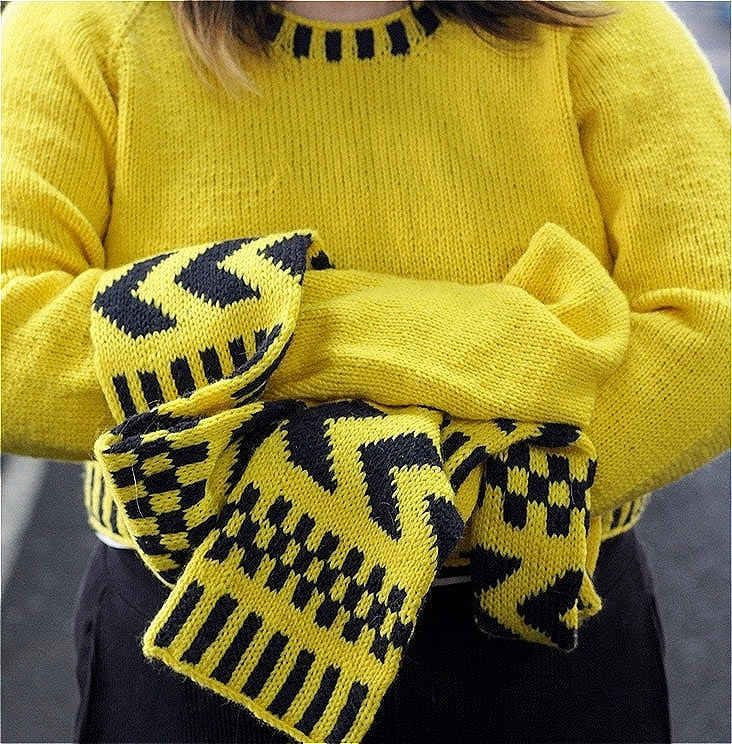 The artist, Sophia Cai, is wearing a yellow handknitted garment with extra long sweater sleeves measuring 1.5 metres, as a response to the social distancing rule. Her arms are folded and the photo is taken in a parking lot.