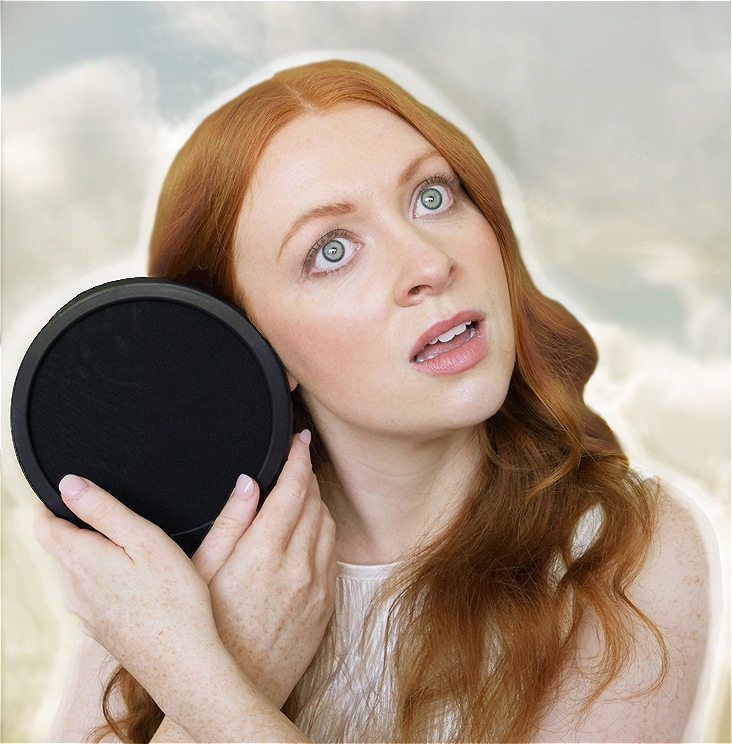 A young woman with pale skin and red hair. She is cradling a pop filter next to her right ear and gazing vacantly into space. Behind her is a blurry, cloudy sky.