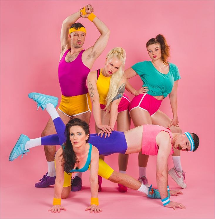 Five performers posing as a group in colourful 80's exercise clothes.
