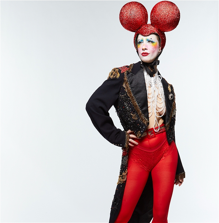 Character wearing Mickey Mouse style red and glitter headpiece, black coat tails with sequins, beaded necklace top and red tights.