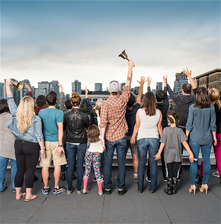A group of people stand with their backs facing the camera, some of whom have their hands upstretched to the sky. Three people are holding a town crier bell in their hands. They are facing a city and the skyline is visible.