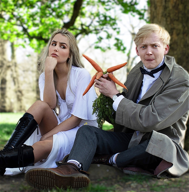 Photo of Alice Fforde and Charlie Dryden sat under a tree. Charlie is holding a bunch of carrots and Alice looks unimpressed.