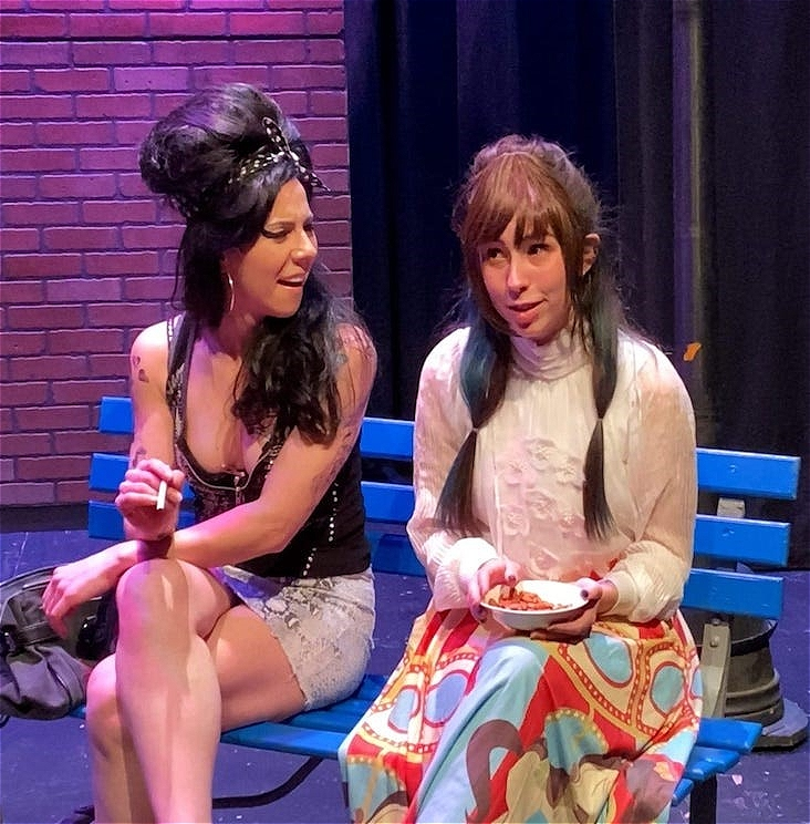 A woman with long black hair wearing a top and mini skirt holds a cigarette while she talks a young woman who is dressed in a jumper and a long skirt.