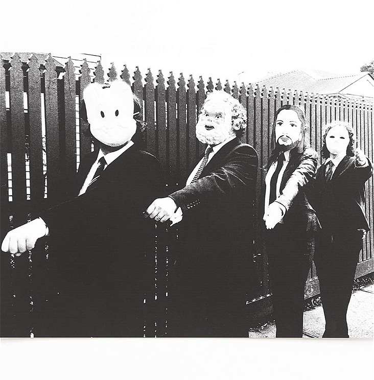 Four people dressed in suits with masks on, raise their left arm perpendicular to their body.
