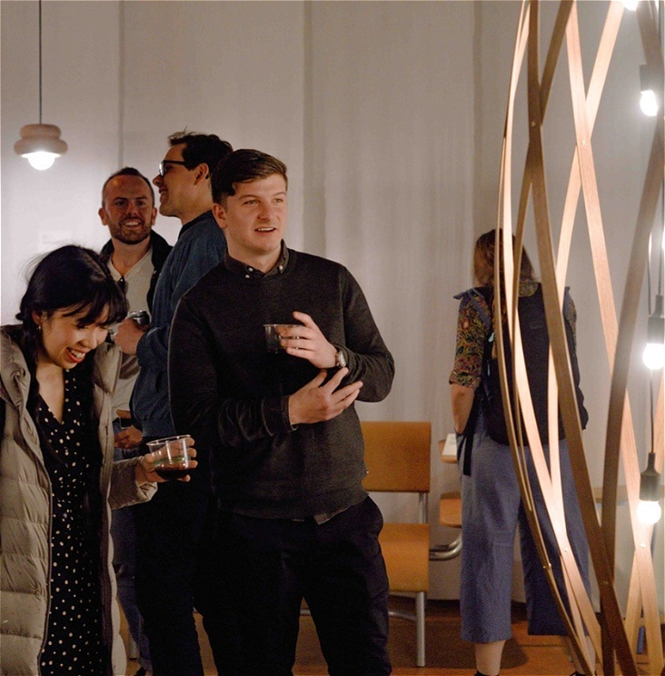 Two people in the foreground of the image laugh and look at a large light fitting.