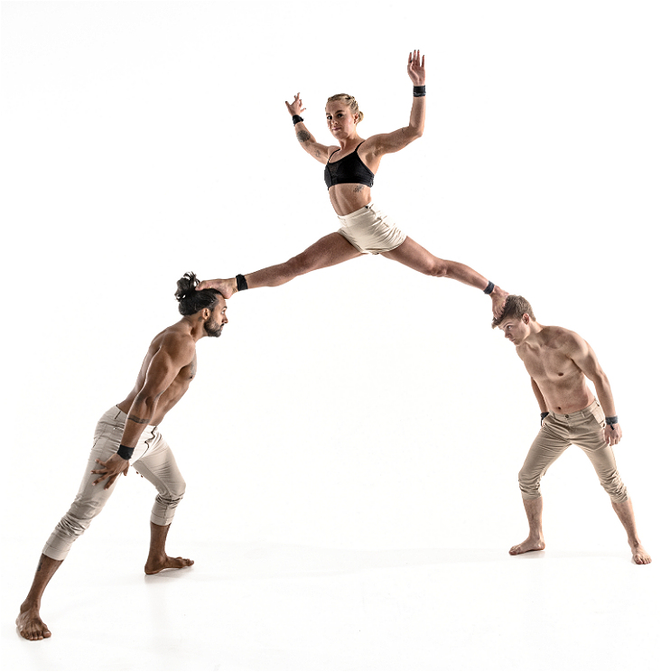 Three acrobats create a triangle shape with the bodies. Two shirtless acrobats in khaki pants are standing, leaning toward each other at a 45 degree angle, staring intently into each others eyes, while the third acrobat, wearing khaki shorts and a black sports bra, balances with their feet on each of the standing acrobats' heads. The balancing acrobat has their arms in the air and stares smiling at the camera.