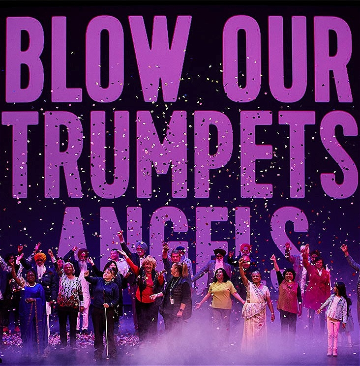 A chorus of thirty community participants of all ages and backgrounds appear on the main stage at Bunjil Place in the City of Casey. They react with unbridled joy as rose petals fall from above the stage. In the background is a large-scale projection of the words 'Blow Our Trumpets Angels'.