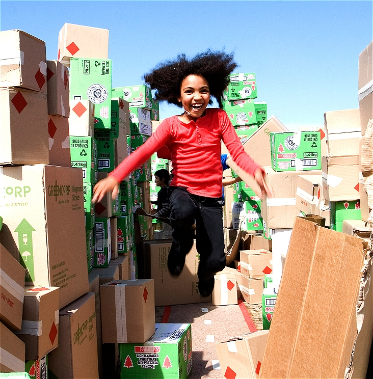 A happy young girl is seen jumping in mid air, she is wearing a red top and black pants. Around her are hundreds of cardboard boxes, some are stacked to create a wall. The image is taken outside and there is a blue sky visible.