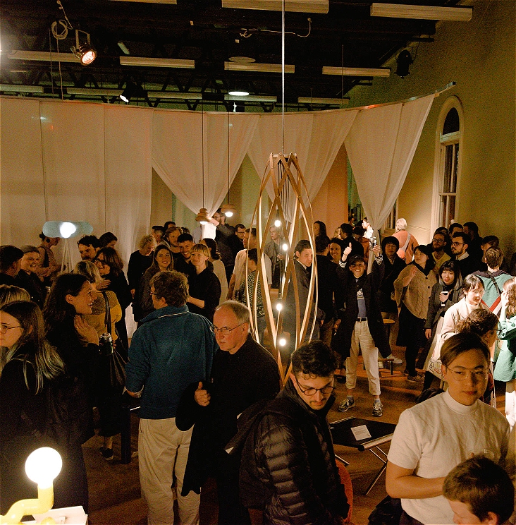 A crowd of people in a furniture exhibition, lit by several lights hanging from the ceiling.