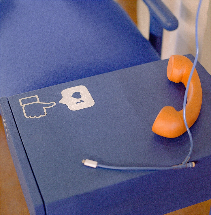 A photo of an orange phone on a blue table. On the table a white thumbs up and an instagram 'like' icon are painted.