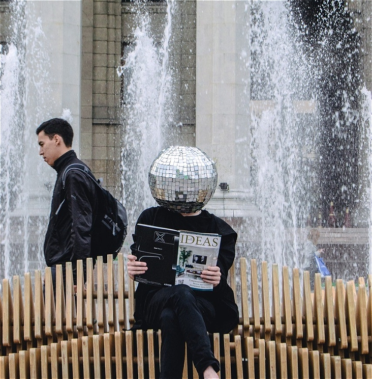 A photo of a person with a mirror ball in place of their head is sitting on an outdoor bench reading an 'IDEAS' magazine. Behind them water is spurting up from a water feature and a person wearing a backpack is walking past in the background.
