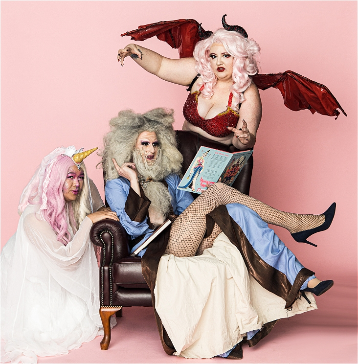 Three people dressed as mythical creatures cluster around a chesterfield armchair; to the left, a pink-haired unicorn is dressed in white; lounging on the chair is a wizard-like creature with bushy hair and a long beard wearing fishnets and heels and reading a book called The Art of Drag; and behind the chair is a pink-haired dragon in a red sparkly bra and big red wings.