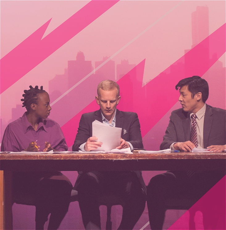 Three figures in suits sit side by side at a desk. The central figure examines paperwork with a concerned look on their face; the figures either side look at each other tensely. The background is a digital image of a cityscape, cut through with geometric shapes, hued in pink.