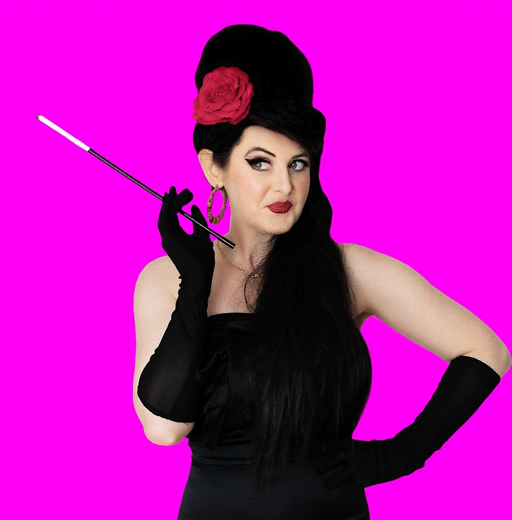 Carol Whitfield dressed as Amy Winehouse in a black dress and Amy Winehouse beehive holding a cigarette in a cigarette holder