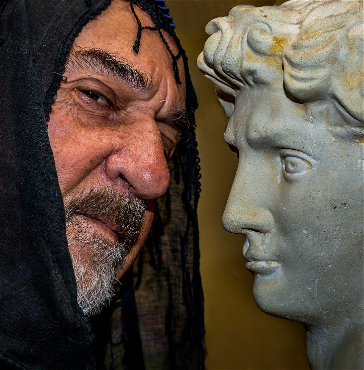 A close up of the face of Odysseus with the head of a statue representing a Greek God.