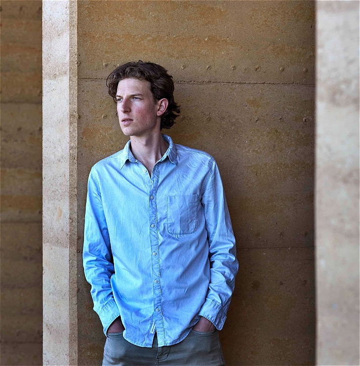 An image of a man leaning against a concrete wall with his hands in his pockets facing away from the camera. He wears a blue button down collared shirt