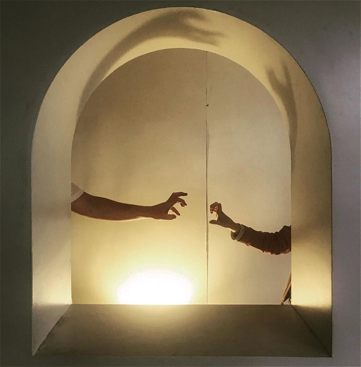 A white painted archway in a thick wall. It is lit from below by warm lamp light. Inside the arch frame are two people's arms reaching towards each other. One person's arm is larger than the other person's arm. The larger arm wears a white t-shirt, the smaller arm a dusty pink jacket sleeve. Their hands are in a gesture that looks as though they might be about to claw each other or maybe they are playfully taunting. On the wall behind the arch window, there is a raised line in the wallpaper or paintwork that runs vertically in frame between the people's arms. In the deep frame of the arch are the shadows of their arms and hands, curving with the line of the arch. .