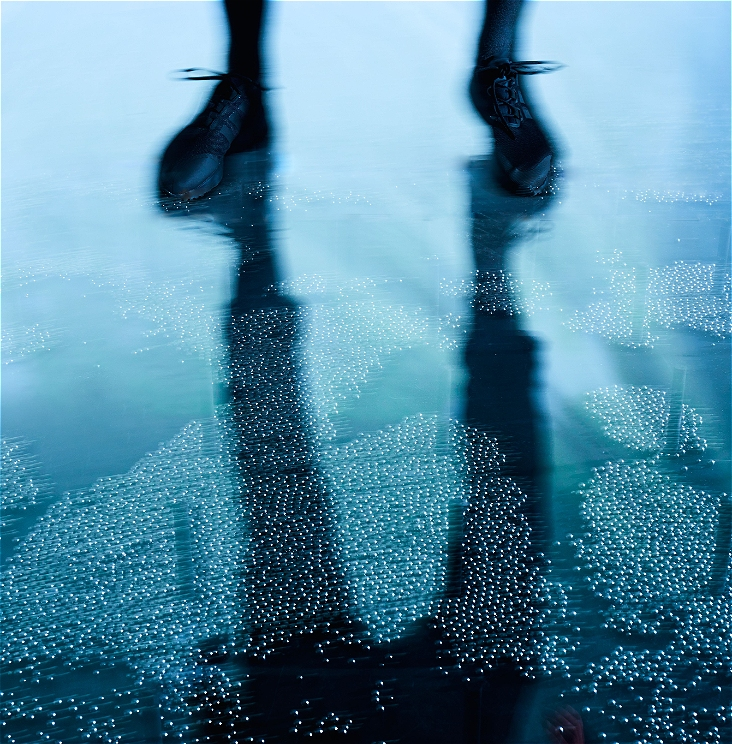 a close cropped image of someone's legs and feet, slightly out of focus standing on top of an clear floor with hundreds of ball bearings underneath