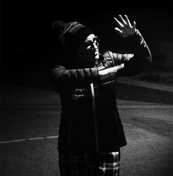 Black and white image of person (performer Chelle Destefano) standing outside under streetlight on a corner of street. Her hands are held up in the air, palms open and she is in mid-sign, signing in Auslan. She is dressed in a coat, checkered pants and a beanie hat and it is a cold night.