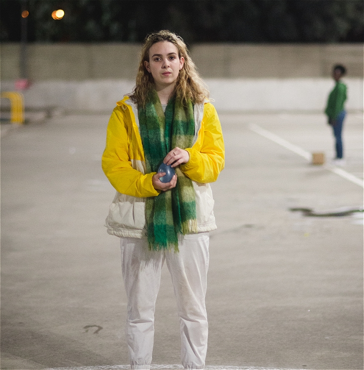 A young woman with blonde hair, a yellow jacket and white pants is standing in a carpark staring directly at the camera.  She is staring in a stern and apathetic manner.  She is gently holding a water balloon with both hands.