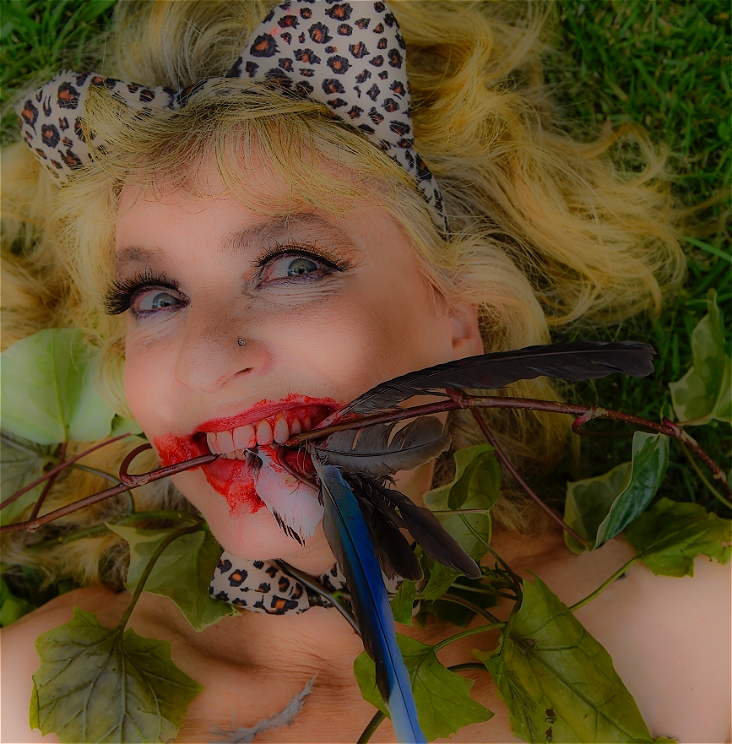 Middle-aged woman, with leopard skin cat ears on her head. A smiling, snarling mouth containing leaves and feathers and spots of bloodstains across her mouth and face.