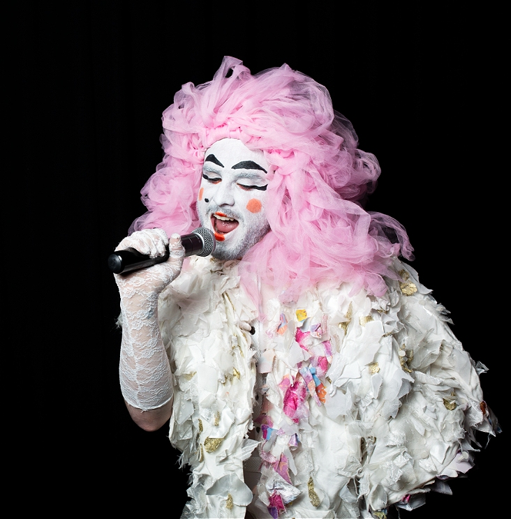 A person in white makeup and pink hair singing into a microphone