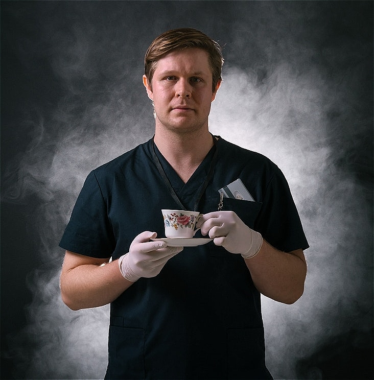 A young man faces the camera wearing dark blue scrubs and holding a flowery china teacup in gloved hands. White smoke billows out behind him.