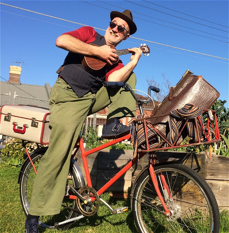 A smiling man is sitting on a red bicycle with luggage in the basket. He is holding a ukulele, and is wearing a hat and sunglasses. The background is blue sky, grass and raised garden beds.