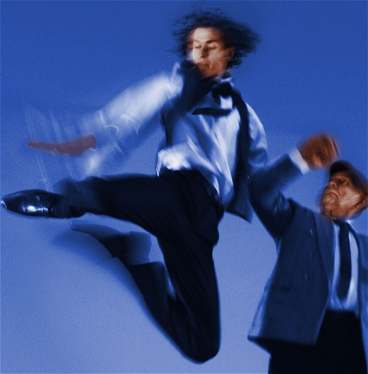 A boy leaps into the air, his legs are bent and he is slapping his right foot. At his left hand side he is supported by an older man who is lifting him up with one hand. The background is blue and the figures are streaky with motion blur.