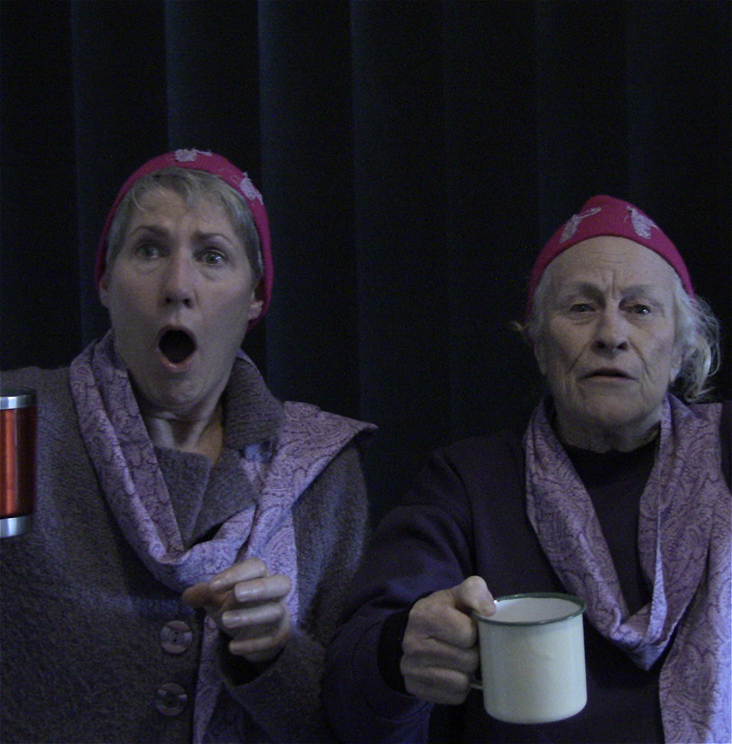 Two senior women seated facing to camera dressed in purple tops and paisley scarves, both wear pink beanies with letters PP in matching paisley print. Younger of the women on left holding red mug looks shocked mouth open while older woman, holding cream mug looks concerned.