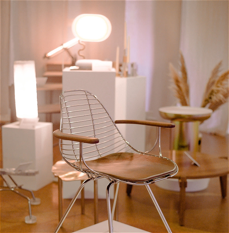 A view of an exhibition with a silver chrome and brown timber and leather chair in the foreground. There are a number of out of focus objects in the background including two lamps sitting on white plinths.