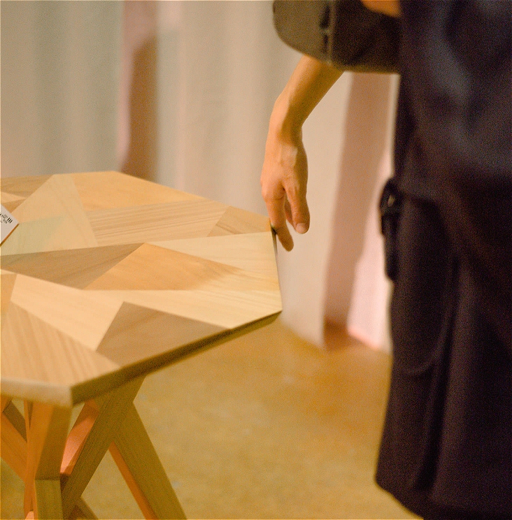 A photo of a timber table made of many triangles of different coloured timber. The back of a hand is touching the table on the edge.