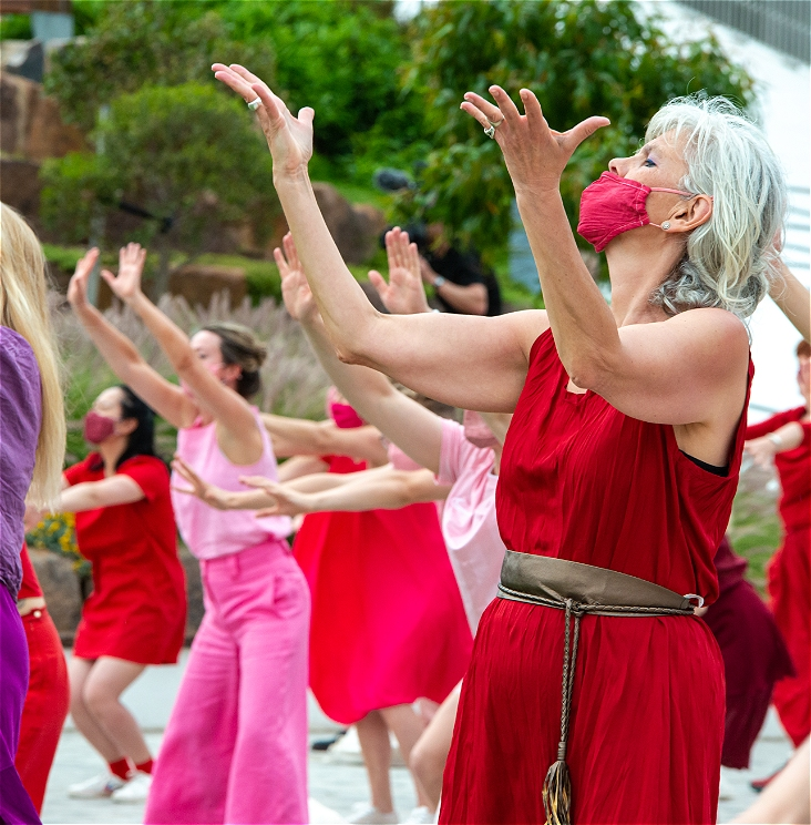 A dancer in red, wearing a red face mask, is performing with their arms raised out in front and hands splayed. Other dancers in red and pink, also with arms raised, are in the background.