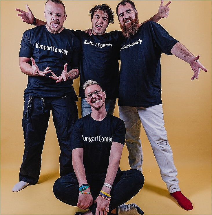 A photo of Stand Up comedians wearing blue tshirts that read