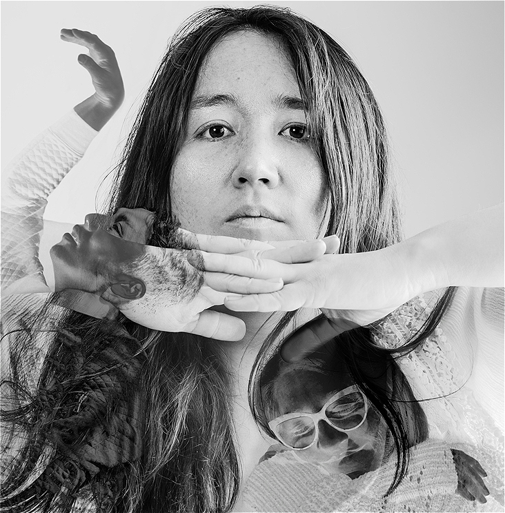 A slightly darker monochrome image of 3 people. Central to this image is a long dark haired person posing with hands interlocked under their chin, arms pointing out to either side. One of the 2 darker overlay images below her hands, is of a person in deep self embrace the other, profile is etched to the left hand side of person at the centre of the image. With their arm held mid air in a beautiful wave like position with their head tilted back they gaze softly at their hand.