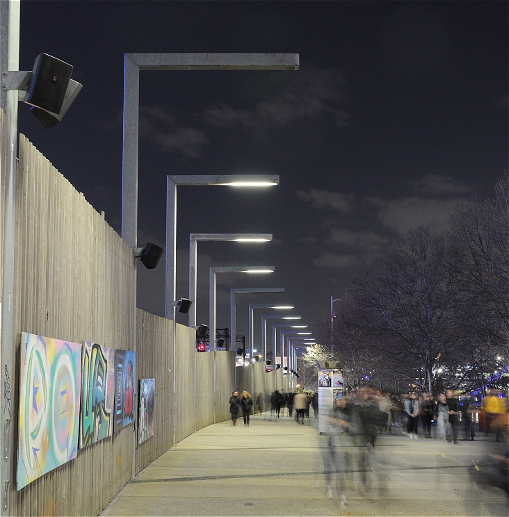 Blurry human figures walk next to a row of speakers along a fence line on a cloudy evening.
