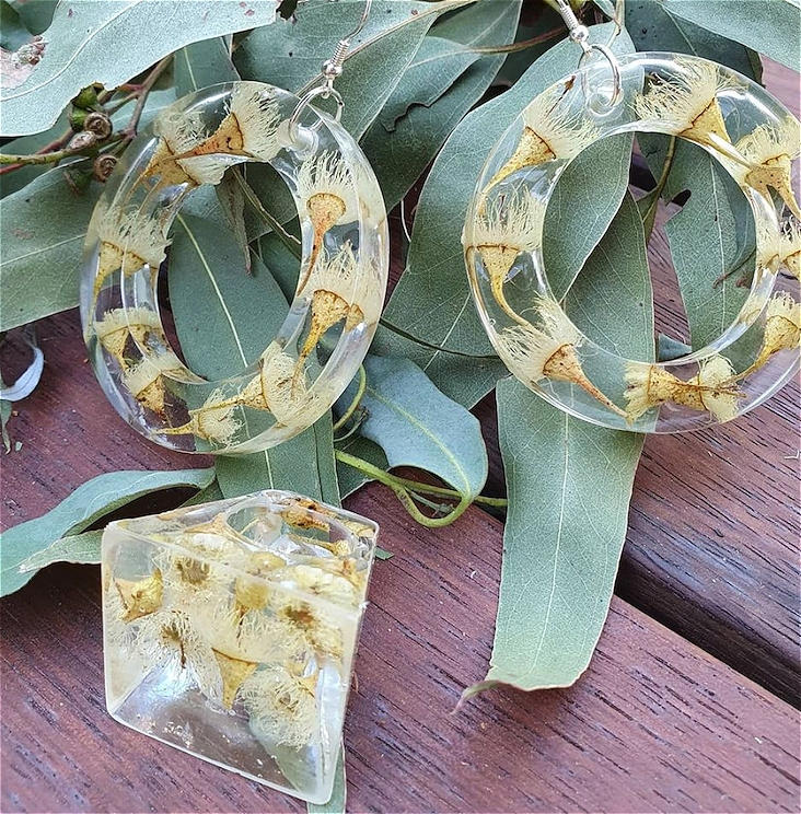 Clear resin embedded yellow gum flowers made into earrings and one finger ring, presented in front of a collection gum leaves on a wooden background.