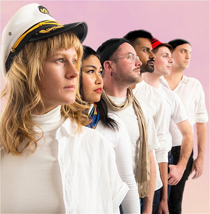 Six people lined up diagonally behind each other in front of a peach background. They are gazing purposefully out to the distance on the right.  The figure at the front is a blond Caucasian woman with shoulder length hair. She is wearing a white turtleneck under a white open collared shirt and a white sailors captain hat with yellow embellishments and a black peak.  The figure behind her is an Asian woman with long dark hair. She is wearing a long sleeved white shirt, a royal blue neck scarf with yellow and orange details.  The figure behind her is a caucasian man with short hair and light stubble. He is wearing a white T Shirt with a grey scarf, clear glasses, a black beanie and a black earring on his left ear.  The figure behind him is a Pakistani man with dark short cropped hair and a short sculpted beard. He is wearing a white collared shirt with the top few buttons undone and the sleeves rolled up to his elbow.  The figure behind him is a clean shaven, white man with short cropped hair. He is wearing a white T shirt and a red and black sailors cap.  The last figure behind him is a clean shaven indigenous man. He is wearing a black beanie and a white collared shirt with the top few buttons undone and sleeves rolled up to his elbow.