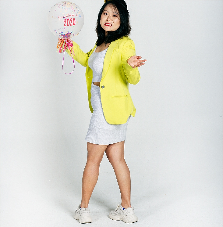 A 30-something Chinese woman holding a birthday balloon with 2020 on it. She wears a bright lemon yellow blazer and a white slim fit and round neck dress with a pair of white sneakers. She shrugs her shoulders and expresses her feelings about