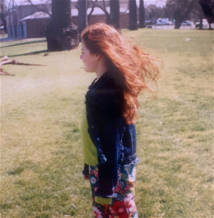 A young girl stands in colourful pants on a grass oval. There is a tree in the background. Her long red hair is blowing in the breeze as she looks into the distance.