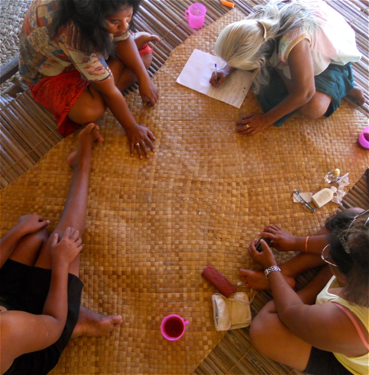 Four brown women sit cross-legged on a woven mat. We can see the tops of their heads as they play a game of cards. One women with white hair is leaning over, keeping score on a piece of paper.