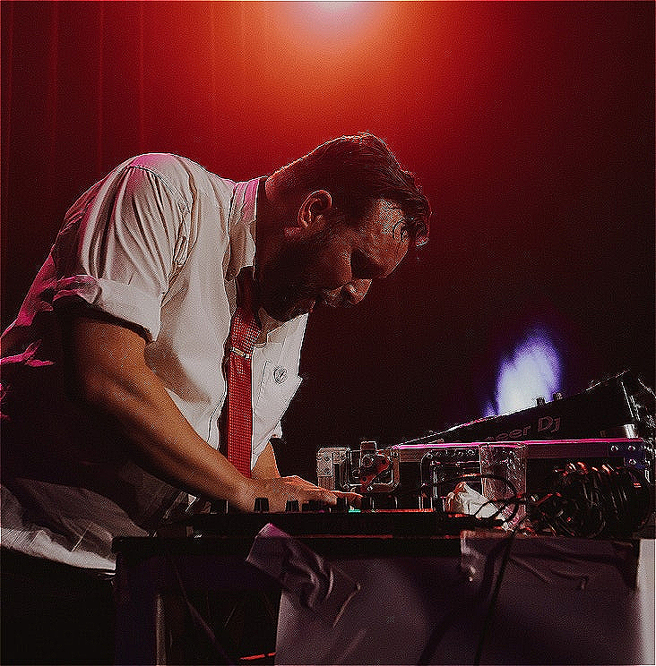 A man wearing a white shirt and red tie leans over a mixing desk.