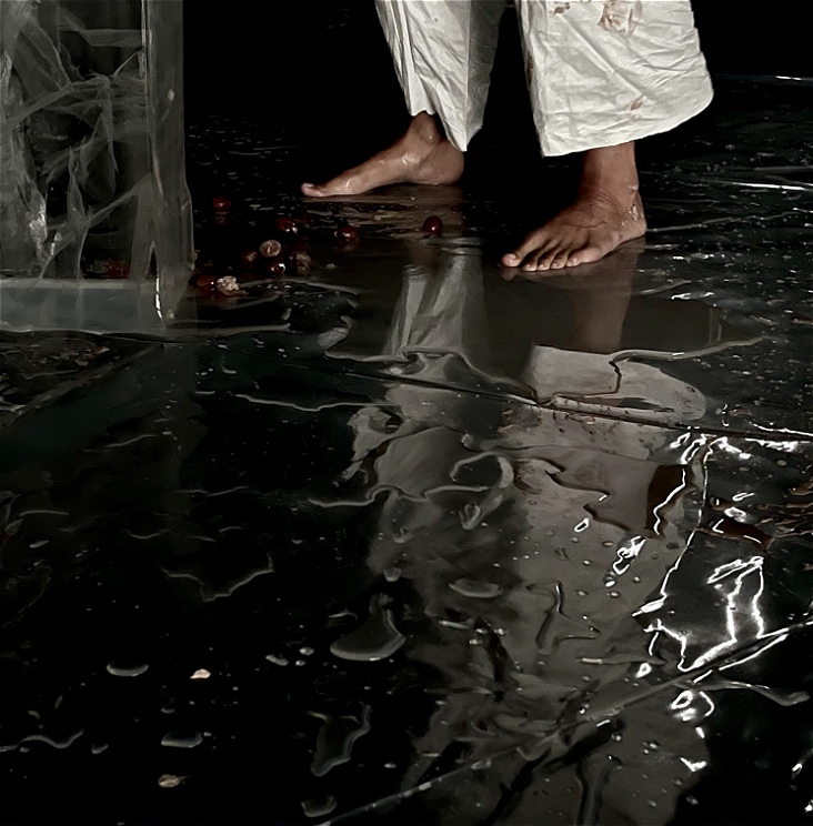 Two legs of a performer can be seen standing on a black, glossy mat, covered in pools of water, next to a large block of ice.